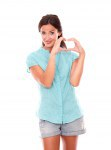 Smiling woman making a love sign with hands