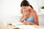 Sophisticated woman thinking while reading a book