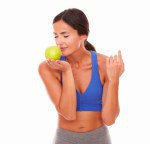 Sporty woman with closed eyes smelling apple