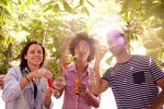 Three funlovers blowing bubbles and laughing