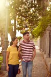 Tourist couple walking down a tree lined street