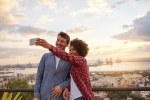 Young couple on bridge taking selfie