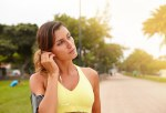 Young jogger listening to music while standing