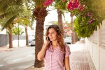 Young woman walking and listening to mobile phone