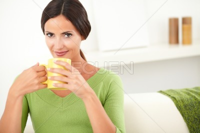 Attractive woman holding a yellow mug