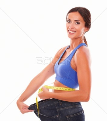 Beautiful adult woman smiling and measuring waist