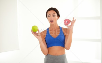 Beautiful brunette on a diet holding food