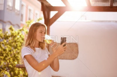 Blond girl with cellpone drinking beer