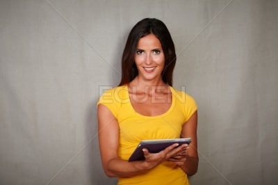 Brunette woman smiling while holding tablet