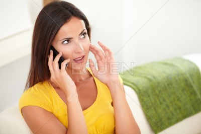 Calm lady thinking while talking on her cell phone