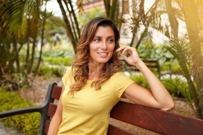 Cheerful lady looking away while sitting on bench