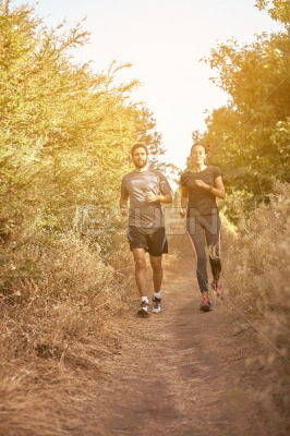 Comfortable couple running down a path