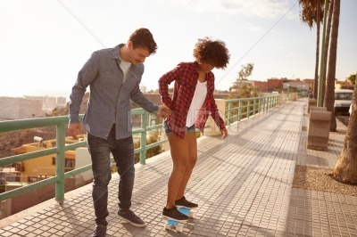 Concentrating young couple learning to skateboard