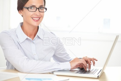 Confident female employee working on laptop