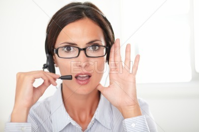 Confident female executive conversing on headset