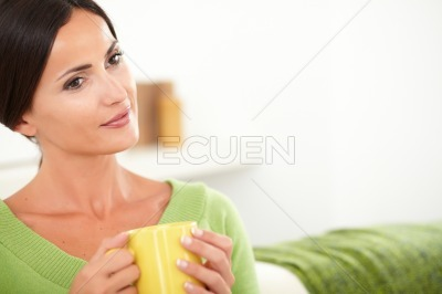 Contemplative woman sitting in the house