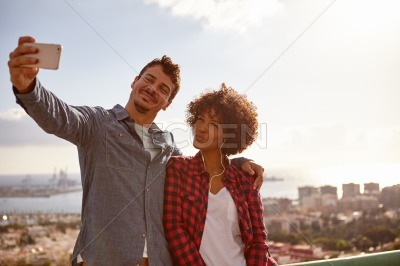 Couple pulling faces to take selfies
