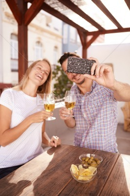 Couple taking selfie with their drinks