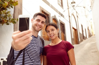 Couple with a backpack, a map taking a selfie