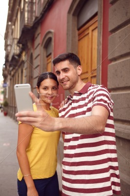 Cute couple taking a selfie in a old part of town