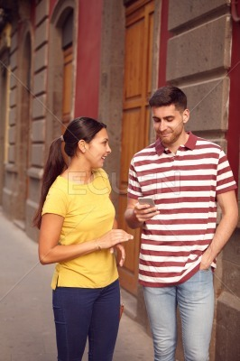 Cute young couple chatting and looking at a cell