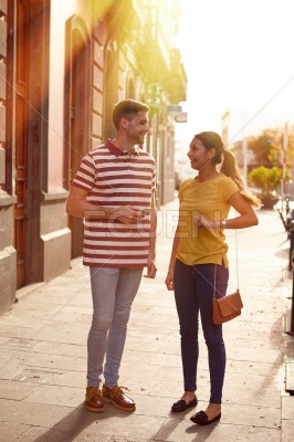 Cute young couple standing on a side walk