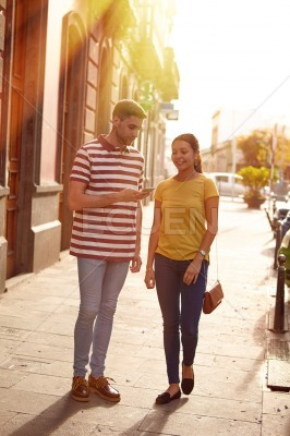 Cute young couple strolling down a side walk