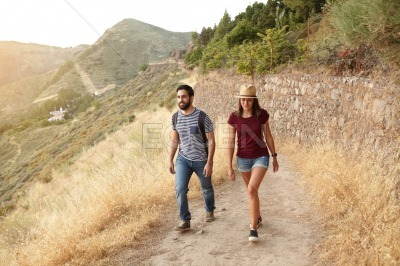 Cute young couple strolling up mountain