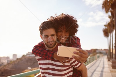 Cute young couple taking playful selfies