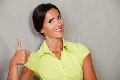 Excited beautiful female with thumb up sign
