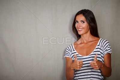 Excited woman showing thumbs up at camera
