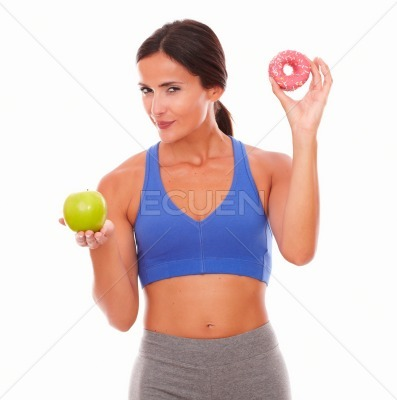 Female in training clothes holding cake and apple