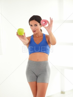Fit female choosing between fruit and donut