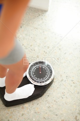 Fit pretty girl weighing herself in a scale