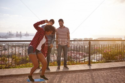 Friends teaching each other to skateboard