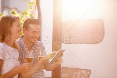 Giggling couple with touchpad and beers