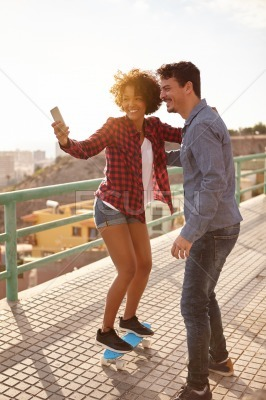 Girl posing on skateboard for selfie