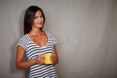 Good-looking brunette female holding coffee cup