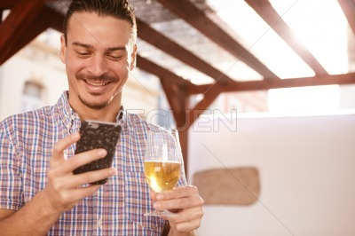 Good looking guy grinning at cellphone
