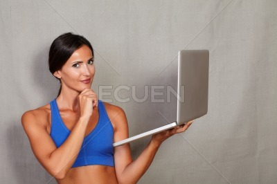Good-looking lady holding laptop with hand on chin