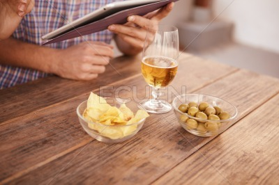 Hands holding touchpad, beer and snacks