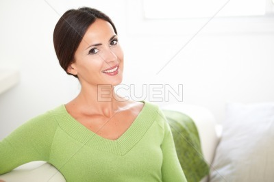 Happy young woman sitting on the couch