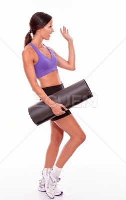 Healthy greeting brunette with yoga mat
