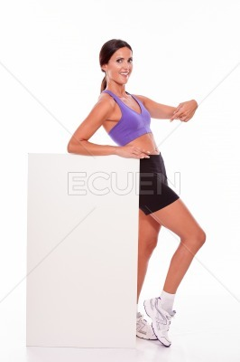 Healthy smiling brunette pointing at placard