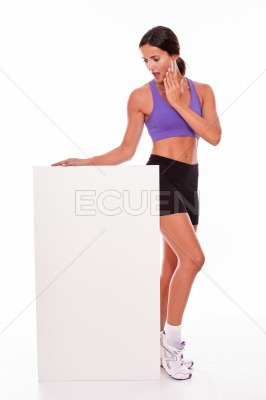 Healthy surprised brunette holding blank placard