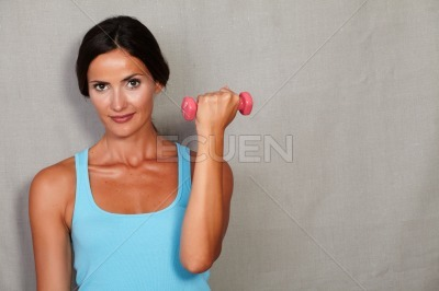 Healthy young woman standing and taking weights