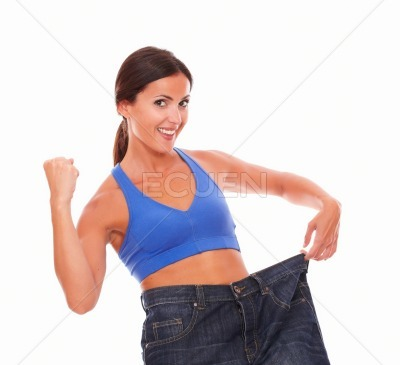 Hispanic brunette female cheerfully pulling jeans