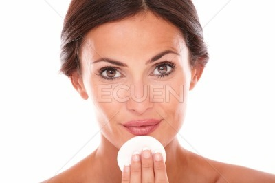 Hispanic woman applying facial care product
