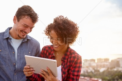Intimate young couple laughing with a tablet