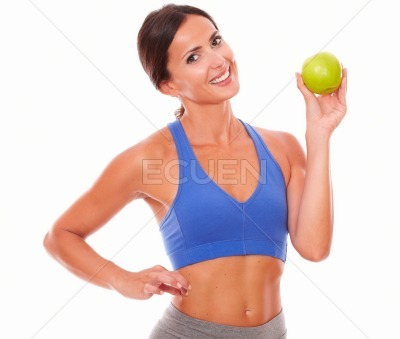 Lady in sportswear showing fruit for fitness